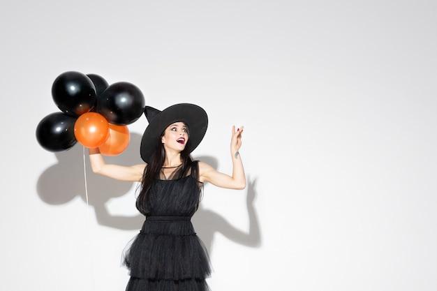 Mujer joven morena con sombrero negro y traje sobre fondo blanco. modelo femenino caucásico atractivo. halloween, viernes negro, cyber monday, ventas, concepto de otoño
