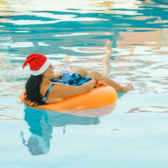 Mujer joven morena con sombrero de santa claus en un círculo de natación en la piscina con un cóctel en la mano
