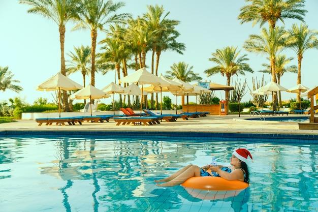 Mujer joven morena con sombrero de santa claus en un círculo de natación en la piscina en las vacaciones de navidad