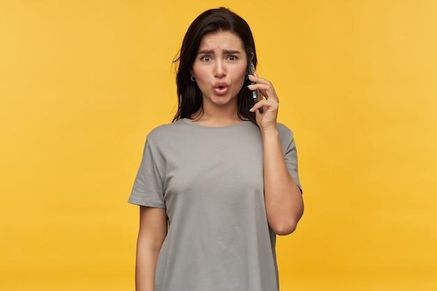 Mujer joven morena sorprendida sorprendida en camiseta gris hablando por teléfono celular sobre pared amarilla