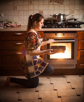 Mujer joven morena sosteniendo pan con galletas cerca del horno