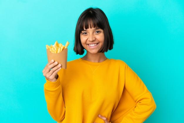 Mujer joven morena sosteniendo patatas fritas sobre fondo azul aislado posando con los brazos en la cadera y sonriendo