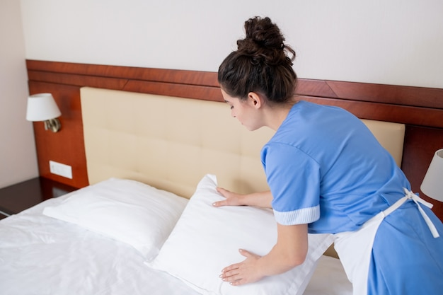 Mujer joven morena en uniforme azul y delantal blanco inclinado sobre la cama mientras cambia las almohadas en la habitación del hotel