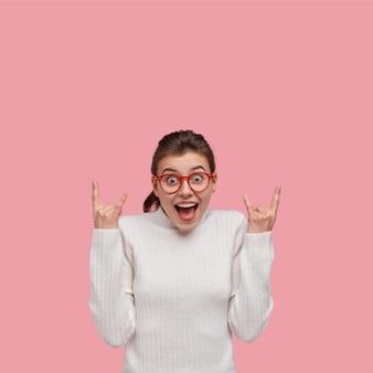 Mujer joven morena vestida con suéter blanco y gafas rojas
