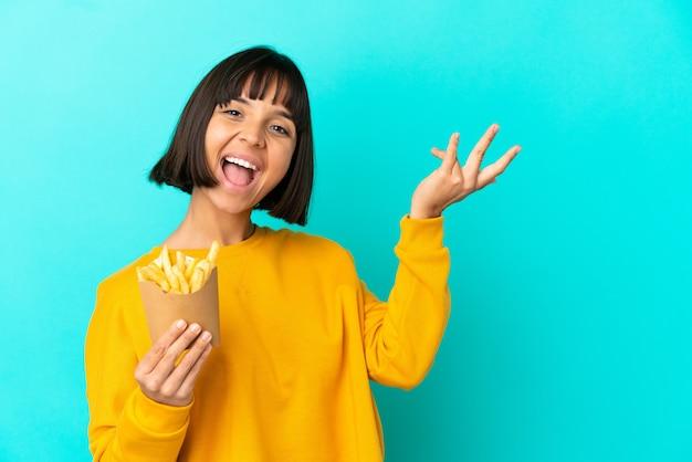 Mujer joven morenita sosteniendo patatas fritas sobre fondo azul aislado extendiendo las manos hacia el lado para invitar a venir