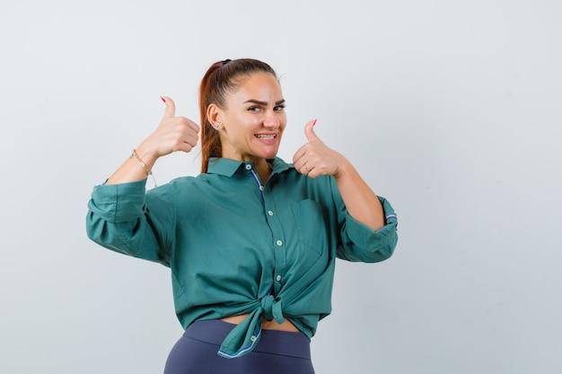 Mujer joven mostrando doble pulgar hacia arriba en camisa verde y mirando contento, vista frontal.