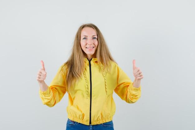 Mujer joven mostrando doble pulgar hacia arriba en chaqueta de bombardero amarilla y jean azul y luciendo optimista, vista frontal.