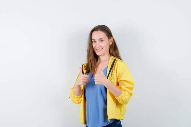 Mujer joven mostrando doble pulgar hacia arriba y mirando confiado, vista frontal.