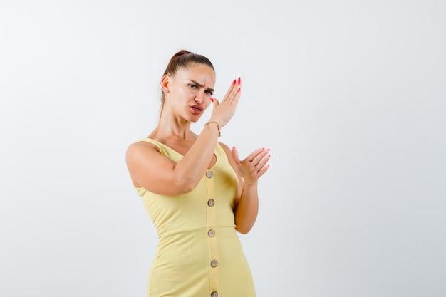 Mujer joven mostrando gesto de chuleta de karate en vestido amarillo y mirando rencoroso, vista frontal.