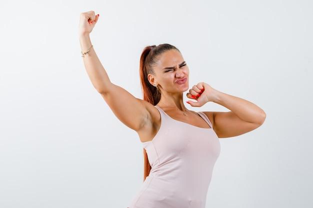 Mujer joven mostrando gesto ganador en camiseta y mirando enérgico, vista frontal.