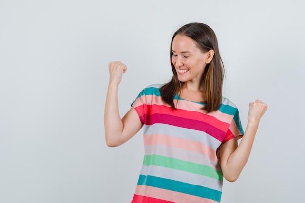 Mujer joven mostrando gesto de ganador en camiseta y mirando feliz, vista frontal.