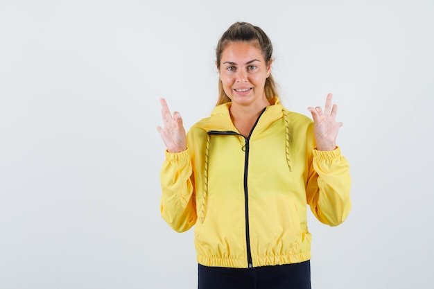 Mujer joven mostrando gesto ok en impermeable amarillo y mirando contento