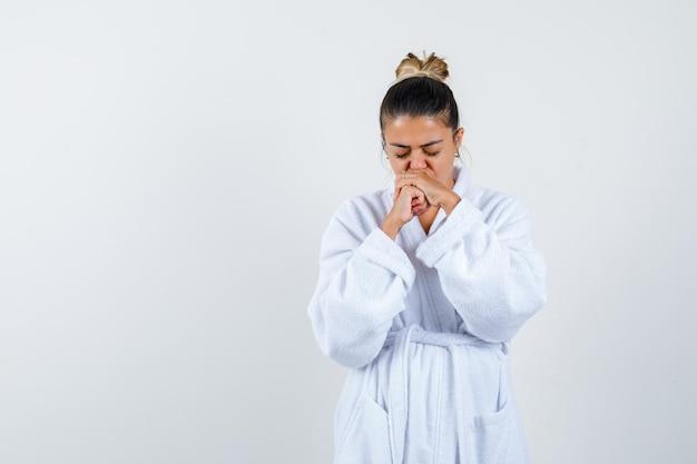 Mujer joven mostrando gesto de oración en bata de baño y mirando esperanzado