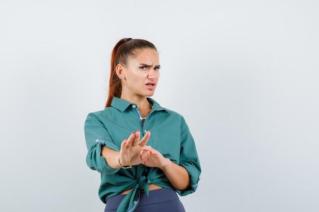 Mujer joven mostrando gesto de parada en camisa verde y mirando disgustado, vista frontal.