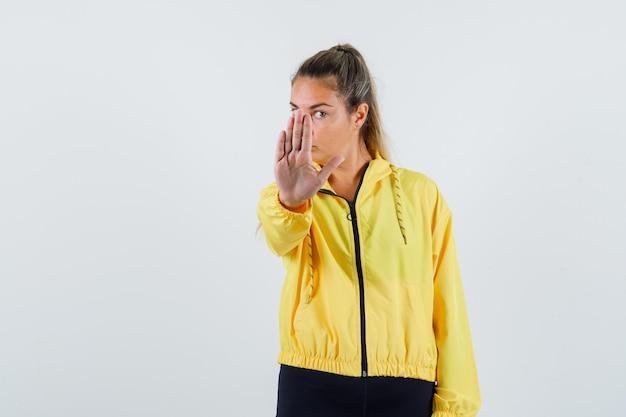 Mujer joven mostrando gesto de parada en impermeable amarillo y mirando serio