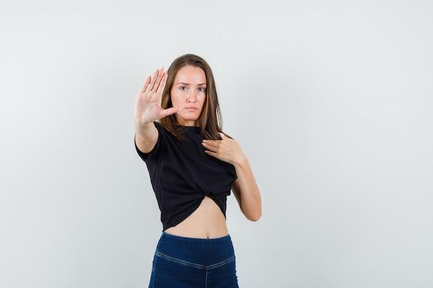 Mujer joven mostrando gesto de parada mientras se señala a sí misma en blusa negra, pantalones y mirando seria.
