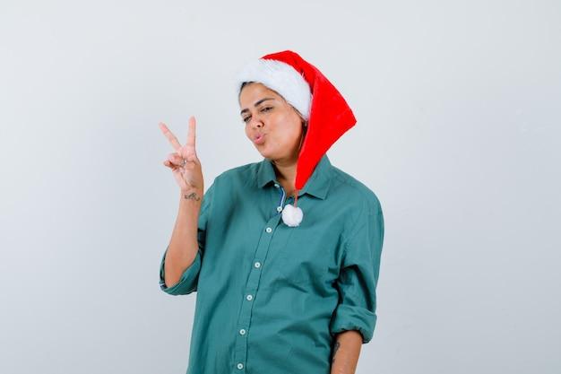 Mujer joven mostrando gesto de paz, haciendo pucheros con los labios en camisa, gorro de papá noel y mirando alegre. vista frontal.