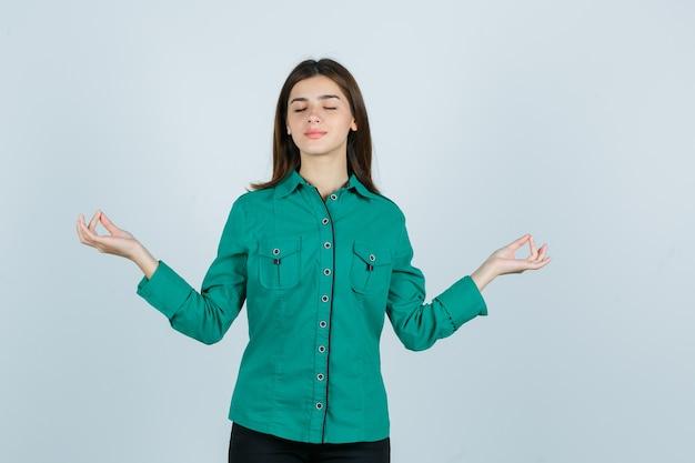 Mujer joven mostrando gesto de yoga con los ojos cerrados en camisa verde y mirando relajado, vista frontal.