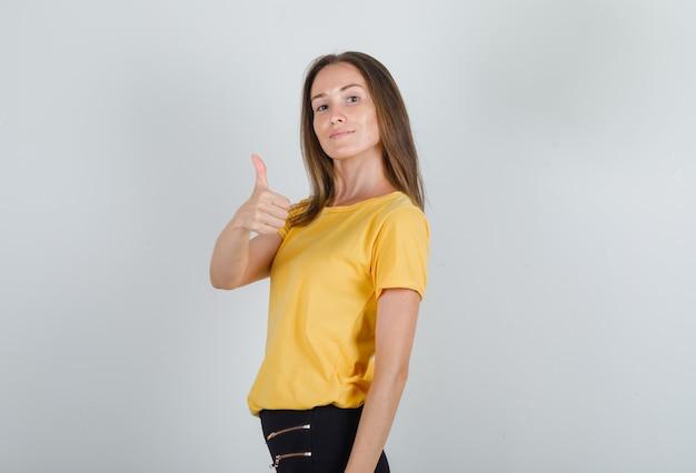 Mujer joven mostrando el pulgar hacia arriba en camiseta amarilla, pantalón negro y mirando complacido.