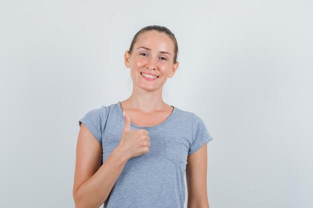 Mujer joven mostrando el pulgar hacia arriba en camiseta gris y mirando feliz, vista frontal.