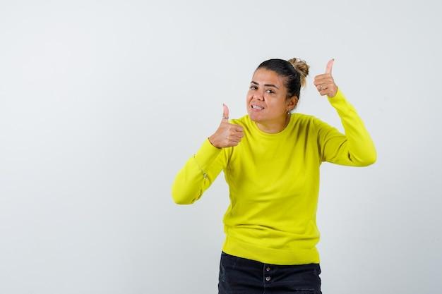 Mujer joven mostrando los pulgares para arriba con ambas manos en suéter amarillo y pantalón negro y mirando feliz