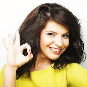 Mujer joven mostrando pulgares arriba gesto