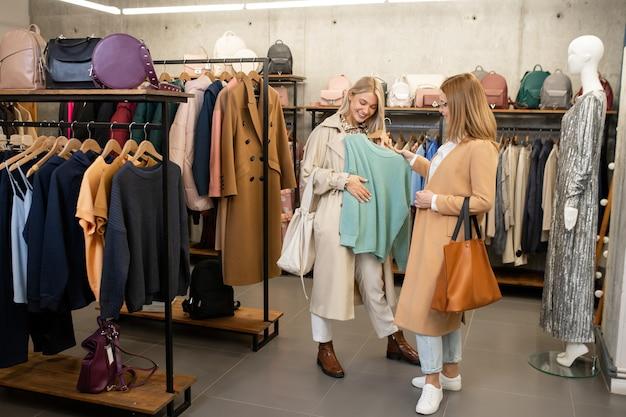 Mujer joven mostrando suéter de algodón azul claro a su amiga mientras elige ropa nueva en el centro comercial durante las compras