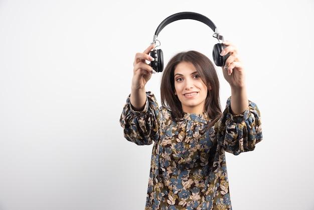 Mujer joven mostrando sus auriculares sobre fondo blanco.