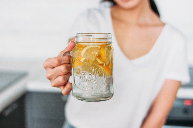 La mujer joven de la muchacha delgada que sostiene el tarro de cristal con agua del limón en cocina