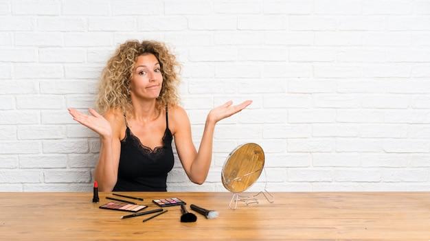 Mujer joven con mucho pincel de maquillaje en una mesa que tiene dudas con expresión de la cara confusa