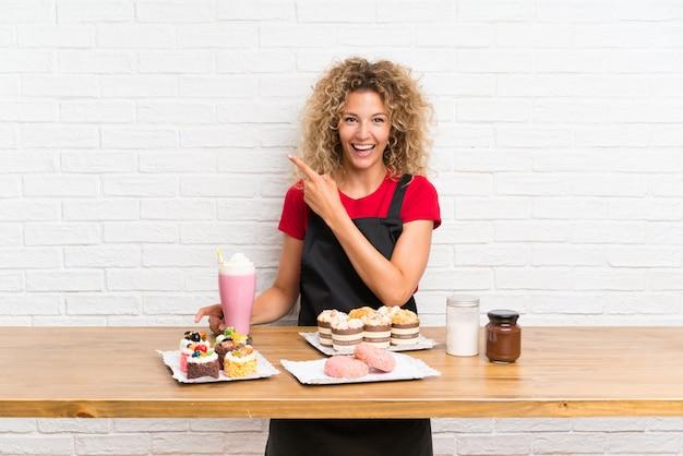 Mujer joven con muchos mini pasteles diferentes en una mesa, apuntando el dedo hacia un lado