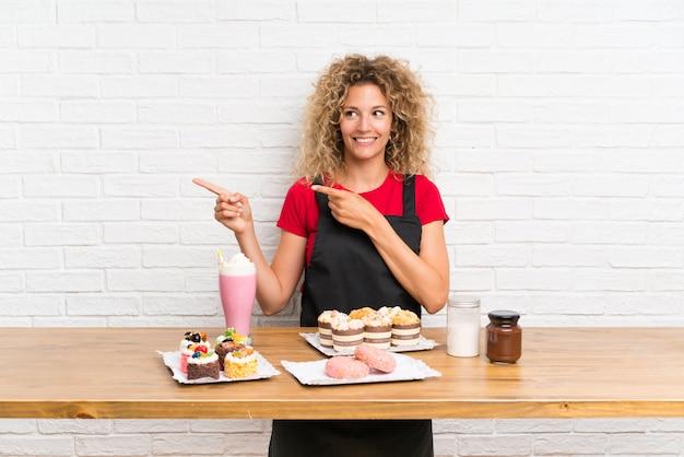 Mujer joven con muchos mini pasteles diferentes en una mesa, apuntando con el dedo hacia un lado