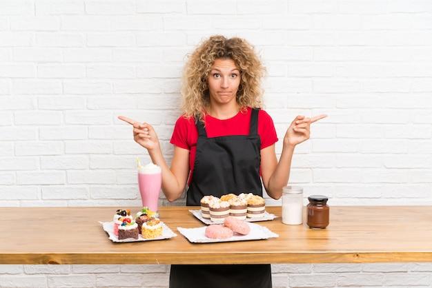 Mujer joven con muchos mini pasteles diferentes en una mesa apuntando a los laterales que tienen dudas