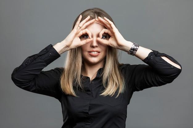 La mujer joven muestra el signo de ok cerrando los ojos. signos y símbolos masónicos, la teoría de la conspiración mundial. hermosa rubia con una camisa negra. fondo gris.