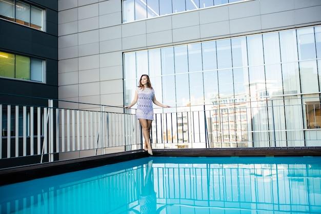 Mujer joven mujer en vestido de encaje hermoso junto a la piscina en la azotea