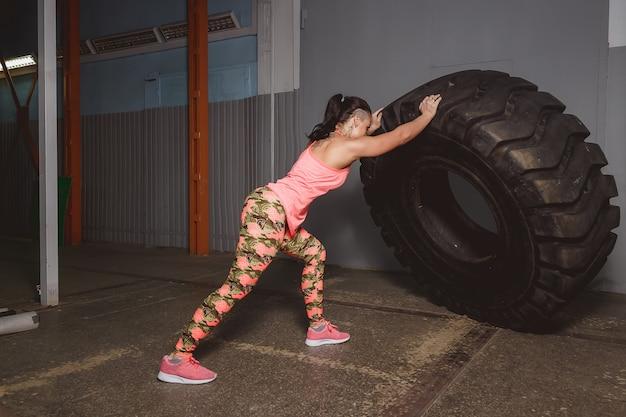 Mujer joven muscular que mueve de un tirón el neumático en el gimnasio. atleta femenina en forma que realiza un tirón del neumático en el gimnasio crossfit.