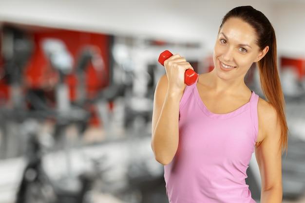 Mujer joven muscular que presenta en la ropa de deportes aislada