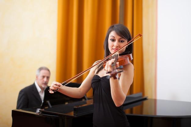 Mujer joven músico tocando su violín