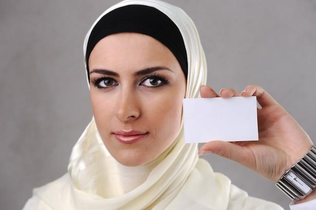 Mujer joven musulmana con tarjeta de visita en mano