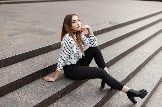 Mujer joven muy atractiva con una blusa de rayas vintage en jeans con estilo en zapatos de cuero de moda se sienta en las escaleras de la ciudad en un cálido día de primavera.