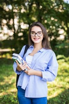 Mujer joven muy atractiva con libros de pie y sonriendo en el parque
