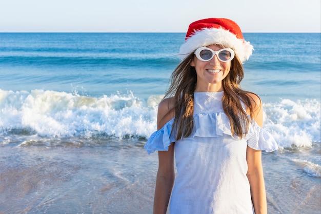 Una mujer joven muy divertida brilla y se regocija con un sombrero de santa claus. navidad niña en gafas de sol