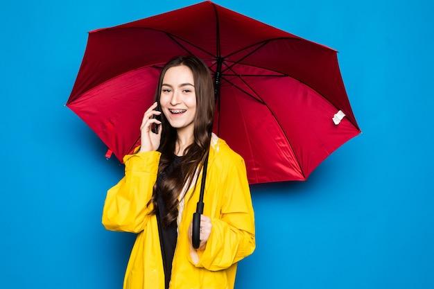Mujer joven muy sonriente feliz con el paraguas que usa el teléfono inteligente en el día de otoño sobre la pared azul colorida