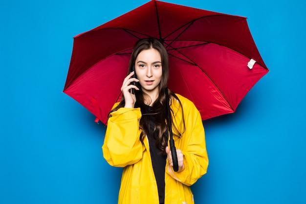 Mujer joven muy sonriente feliz con el teléfono inteligente de la charla del paraguas en el día de otoño sobre la pared azul colorida