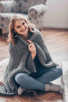 Mujer joven muy sonriente se sienta cerca de la fogata en otoño o casa del bosque. concepto de relax de invierno.