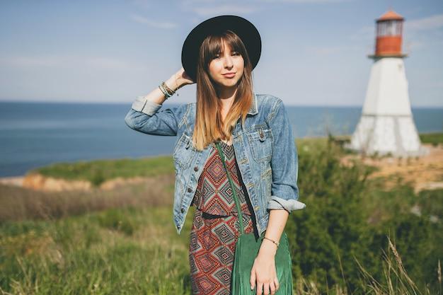 Mujer joven en la naturaleza, faro, traje bohemio, chaqueta vaquera, sombrero negro, sonriente, feliz, verano, accesorios elegantes