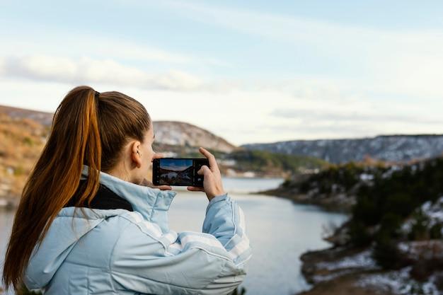 Mujer joven en la naturaleza tomando fotos