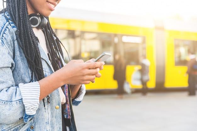 Mujer joven negra escribiendo en un teléfono inteligente en berlín