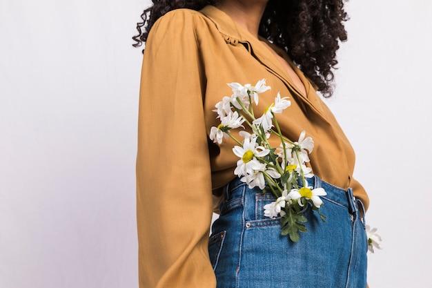 Mujer joven negra con flores en el bolsillo de los pantalones vaqueros.