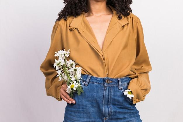 Mujer joven negra con flores de margarita en el bolsillo de los pantalones vaqueros